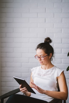 W średnim wieku atrakcyjna kobieta patrzeje pastylkę szuka online.