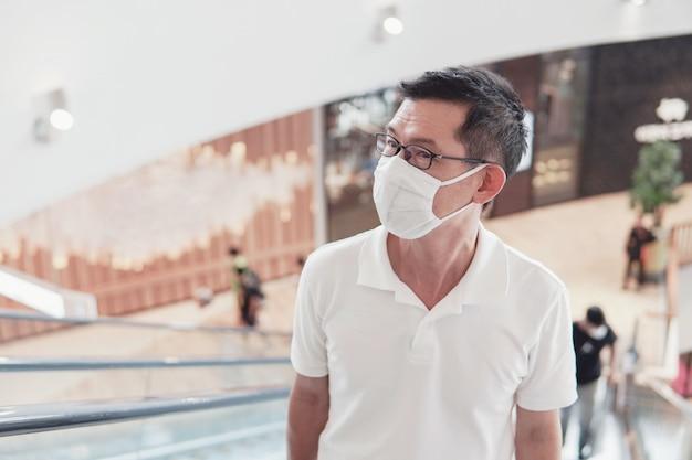 W średnim wieku azjatycki mężczyzna jest ubranym szkła i medyczną twarzy maskę w zakupy centrum handlowym, wuhan coronavirus wybuchu, zanieczyszczeniu powietrza i zdrowia pojęciu