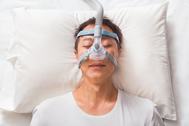 W średnim wieku azjatycki mężczyzna śpi w swoim łóżku na sobie maskę cpap dla osób z bezdechem sennym