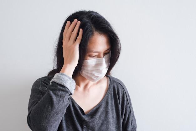 W średnim wieku azjatykcia kobieta jest ubranym ochronną maskę