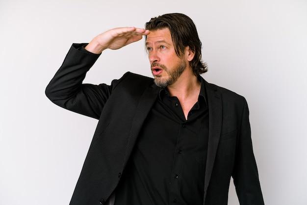 W średnim wieku biznes holenderski mężczyzna na białym tle na białej ścianie, patrząc daleko, trzymając rękę na czole