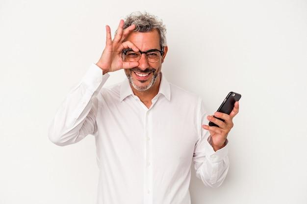 W średnim wieku biznes kaukaski człowiek posiadający telefon komórkowy na białym tle podekscytowany utrzymanie ok gest na oko.