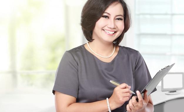 W średnim wieku biznesowa kobieta trzyma schowek