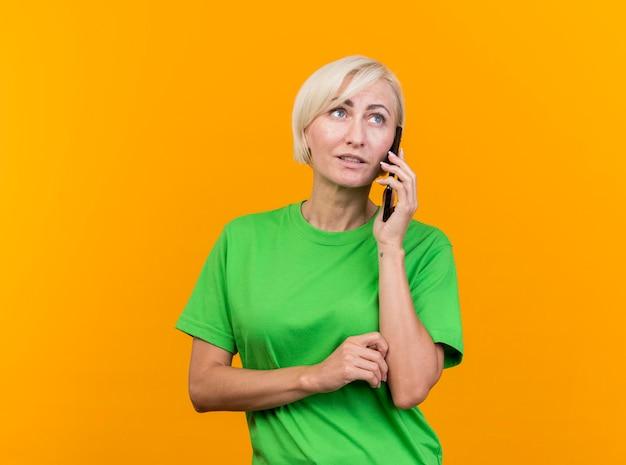 W średnim wieku blond słowiańska kobieta rozmawia przez telefon, patrząc na bok na białym tle na żółtej ścianie z miejsca na kopię
