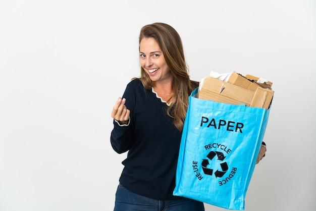 W średnim wieku brazylijska kobieta trzyma worek recyklingu pełen papieru do recyklingu na izolowanej ścianie, zarabianie gest pieniędzy