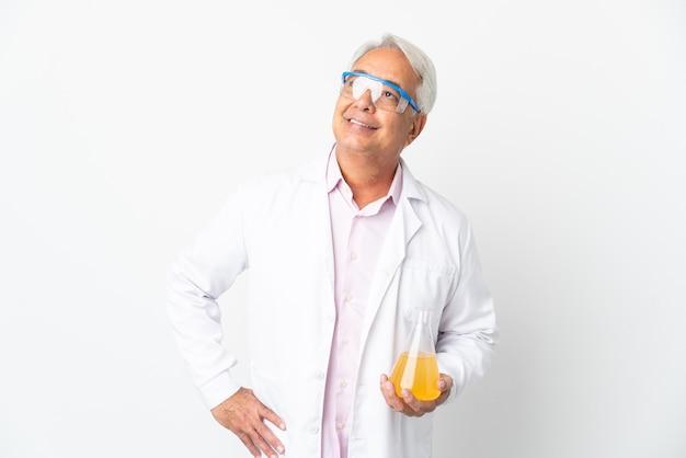 W średnim wieku brazylijski naukowiec naukowy na białym tle na białej ścianie pozowanie z rękami na biodrze i uśmiechnięty