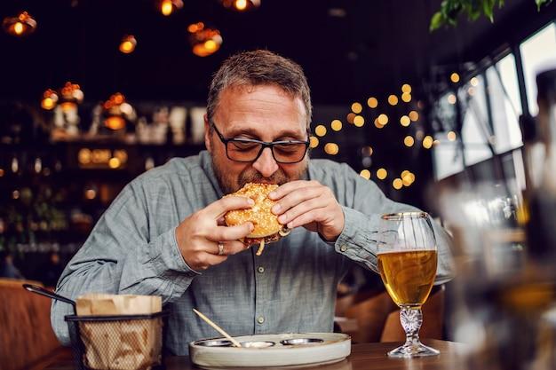 W średnim wieku brodaty głodny mężczyzna siedzi w restauracji i je pysznego burgera.