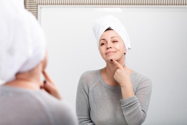 W średnim wieku caucasian kobieta z kąpielowym ręcznikiem na głowie
