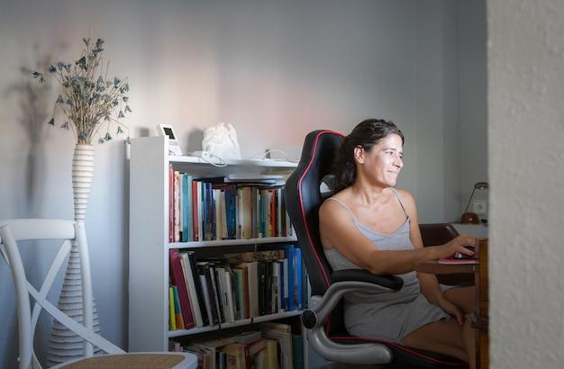 W średnim wieku hiszpańska brunetka telepracuje w domowym biurze z książkami