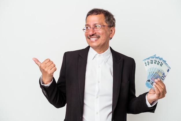 W średnim wieku indyjski biznesmen posiadający rachunki na białym tle wskazuje palcem kciuka, śmiejąc się i beztrosko.