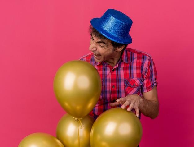 W średnim wieku kaukaski mężczyzna ubrany w kapelusz partii stojącej za balonami szykując się do ugryzienia jednego na białym tle na szkarłatnym tle