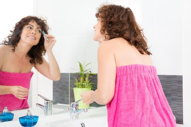 W średnim wieku kędzierzawa kobieta w różowym ręczniku nakładającym korektor do oczu przed lustrem