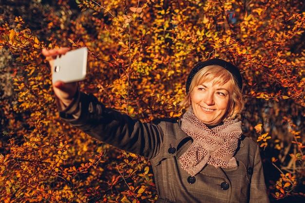 W średnim wieku kobieta bierze selfie na telefonie w jesień lesie