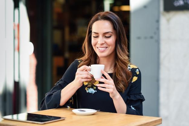 W średnim wieku kobieta pije kawę w miejskiej kawiarni.