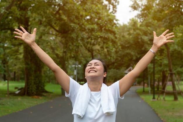 W średnim wieku kobieta pokazuje wygranie i jogging w parku.