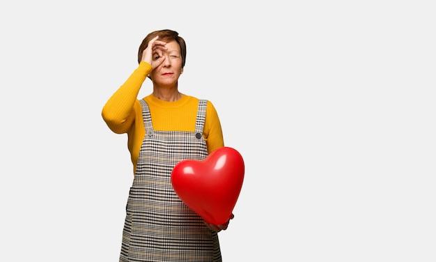 W średnim wieku kobieta świętuje valentines dzień robi gestowi spyglass