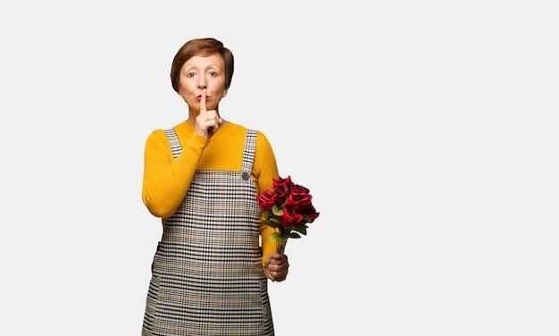 W średnim wieku kobieta świętuje valentines dzień utrzymuje sekret lub pyta dla ciszy