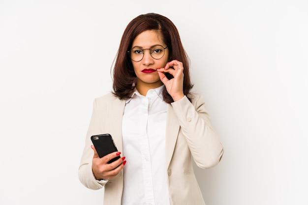 W średnim wieku kobieta trzyma telefon komórkowego z palcami na wargach utrzymuje sekret