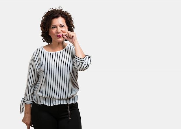 W średnim wieku kobieta utrzymuje sekret lub pyta dla ciszy, poważnej twarzy, posłuszeństwa pojęcia