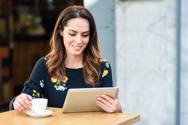W średnim wieku kobieta używa pastylkę na kawowej przerwie w miastowym kawiarnia barze
