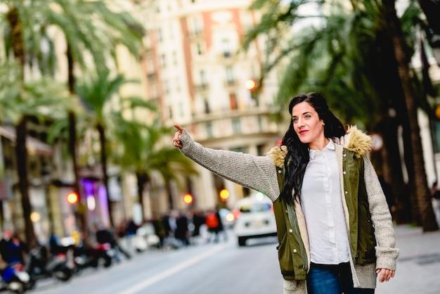 W średnim wieku kobieta wita taxi z jej ręką podnoszącą w ulicie.
