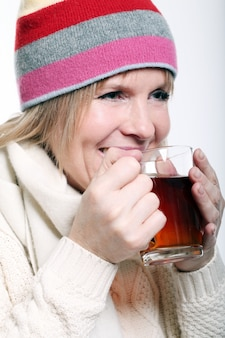 W średnim wieku kobieta z gorącą herbatą jest ubranym zimę odziewa na białym tle