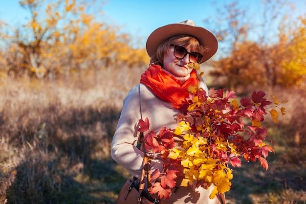 W średnim wieku kobiety mienia bukiet jesieni gałąź