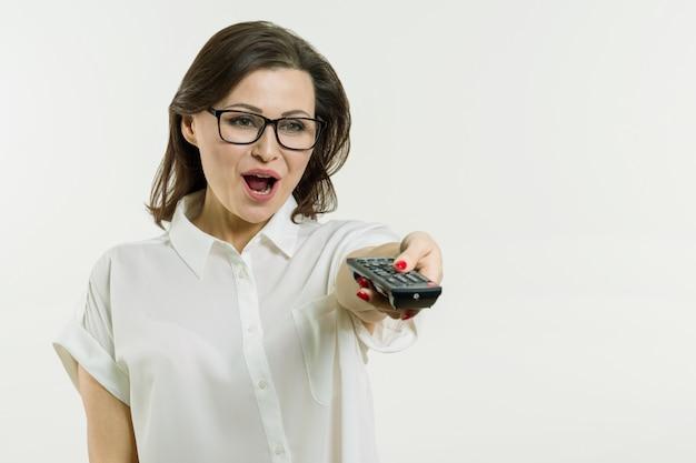 W średnim wieku kobiety mienia pilot do tv