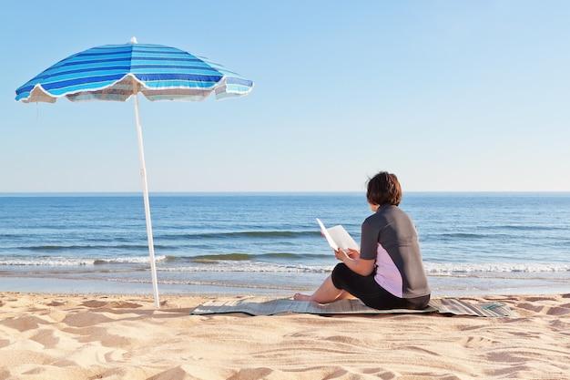 W średnim wieku kobiety obsiadanie na plaży czyta książkę. pod parasolem plażowym.