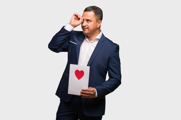 W średnim wieku łaciński mężczyzna świętuje valentines dzień robi gestowi spyglass