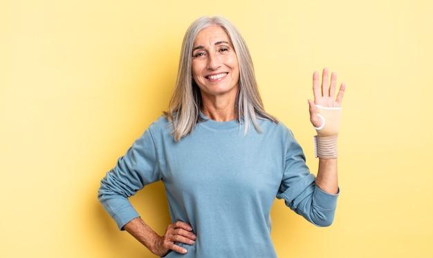 W średnim wieku ładna kobieta uśmiechnięta radośnie z ręką na biodrze i pewna siebie. koncepcja bandaża ręcznego