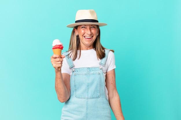 W średnim wieku ładna kobieta w kapeluszu i trzymając loda. koncepcja lato