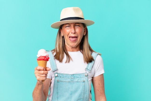 W średnim wieku ładna kobieta w kapeluszu i trzymając lody. koncepcja lato