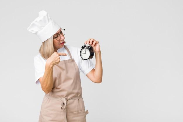 W średnim wieku ładna piekarz kobieta trzyma budzika