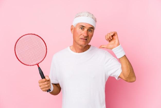 W średnim wieku mężczyzna bawić się badminton odizolowywającego pokazywać niechęć gest, kciuki zestrzela. pojęcie nieporozumienia.
