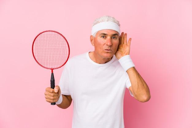W średnim wieku mężczyzna bawić się badminton odizolowywał próbować słuchać plotki.