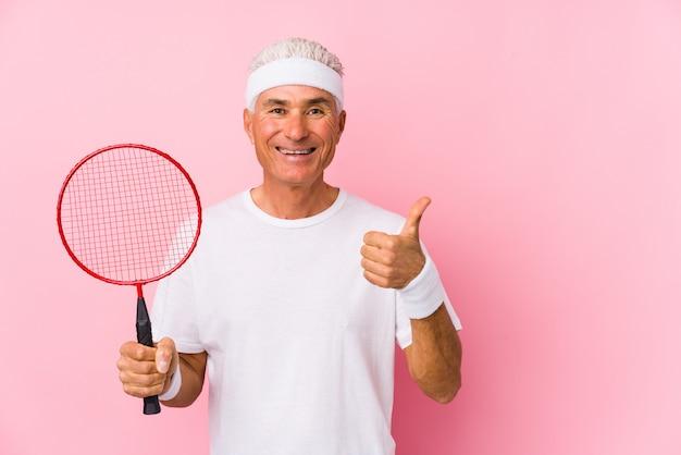 W średnim wieku mężczyzna bawić się badminton odizolowywał uśmiecha się kciuk up i podnosi