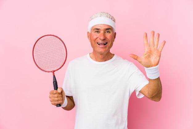 W średnim wieku mężczyzna bawić się badminton odizolowywał uśmiechniętego rozochoconego seans liczbę pięć z palcami.