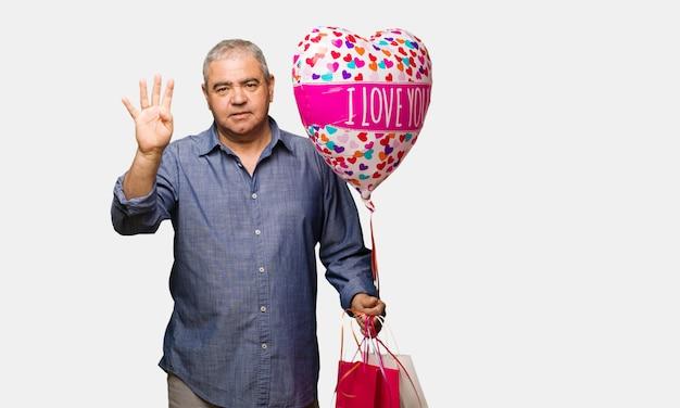W średnim wieku mężczyzna odświętności valentines dzień pokazuje liczbę cztery
