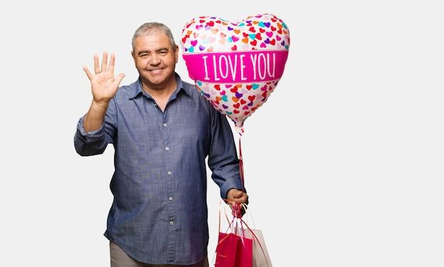 W średnim wieku mężczyzna odświętności valentines dzień pokazuje liczbę pięć
