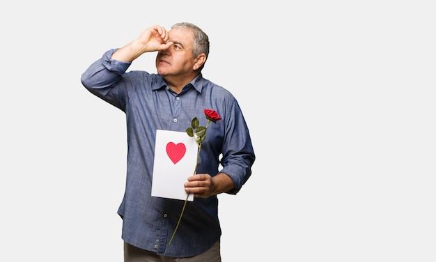 W średnim wieku mężczyzna świętuje valentines dzień robi gestowi spyglass