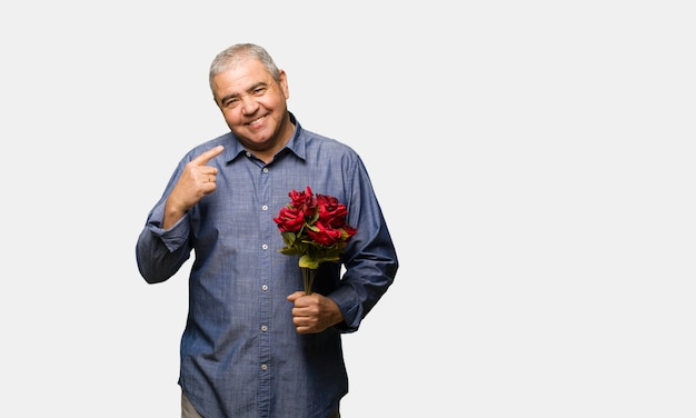 W średnim wieku mężczyzna świętuje valentines dzień uśmiecha się, wskazujący usta