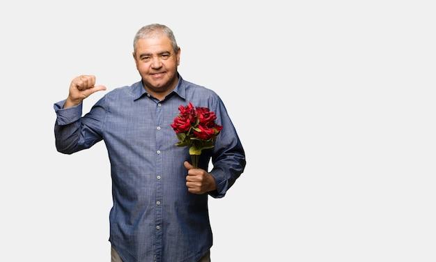 W średnim wieku mężczyzna świętuje valentines dzień wskazuje palce, przykład podążać