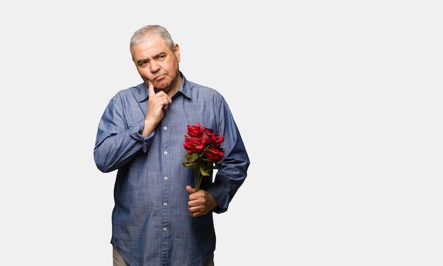 W średnim wieku mężczyzna świętuje valentines wątpić i zmieszany