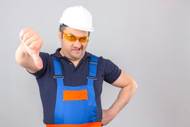 W średnim wieku niezadowolony budowniczy mężczyzna w mundurze konstrukcyjnym i hełmie ochronnym pokazując kciuk w dół na pojedyncze białe ściany