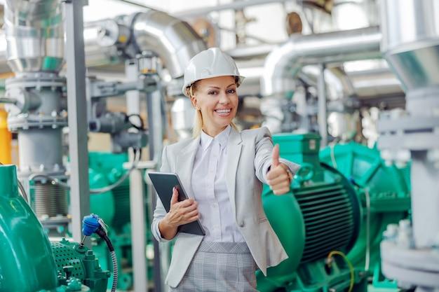 W średnim wieku odnosząca sukcesy blond przełożona kobieta w garniturze z hełmem ochronnym na głowie, stojąca w elektrowni z tabletem w rękach i pokazująca kciuki do góry.
