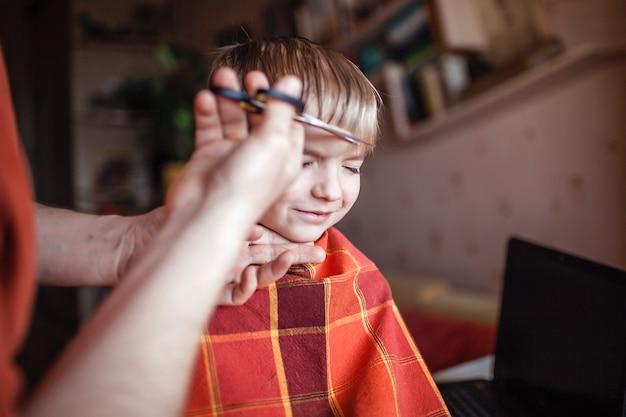 W średnim wieku ojciec sam strzyże włosy swojemu synkowi w domu