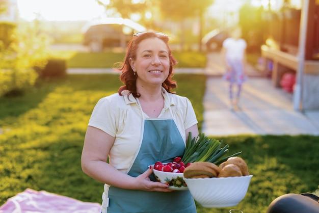 W średnim wieku piękna kobieta trzyma jedzenie w jej rękach