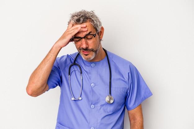 W średnim wieku pielęgniarka kaukaski mężczyzna na białym tle jest zszokowany, przypomniała sobie ważne spotkanie.