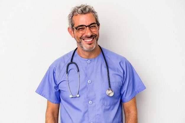 W średnim wieku pielęgniarka kaukaski mężczyzna na białym tle szczęśliwy, uśmiechnięty i wesoły.